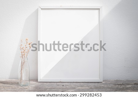 Vintage blank picture frame and sunlight on a wall. - stock photo