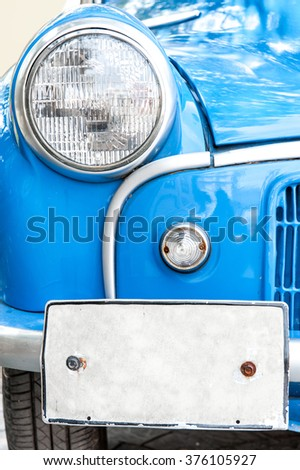 Vintage blue car,head light and licensed plate close up. - stock photo