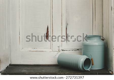 Vintage blue milk canisters in front of rustic door. - stock photo