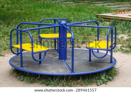 Vintage blue roundabout in empty child playground - stock photo