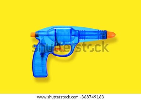 Vintage blue water-gun on yellow background - stock photo