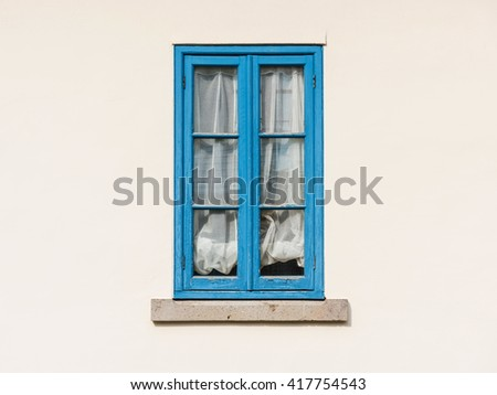 Vintage blue wooden window on white wall - stock photo