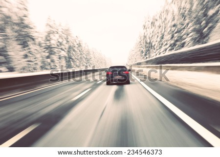 Vintage blurry black car high speed driving on icy winter highway. Motion blur visualizies the speed and dynamics. - stock photo