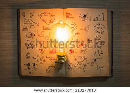 vintage book of business graph and light bulb on wood table - stock photo