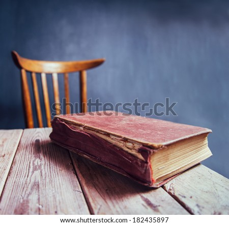 Vintage book on a wooden table in a classroom - stock photo
