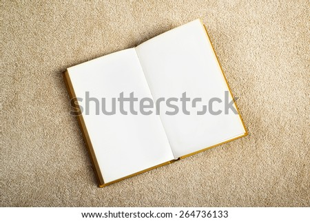 Vintage Book with Blank Pages as Copy Space on the New Beige Carpet Floor, top view - stock photo