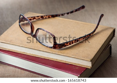 vintage books are stacked on wooden table with a reading glasses - stock photo