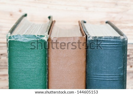 vintage books next to the wooden wall - stock photo
