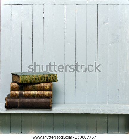 Vintage books on shelf; photographed in a pile against a pale, rustic wall; good copy-space - stock photo