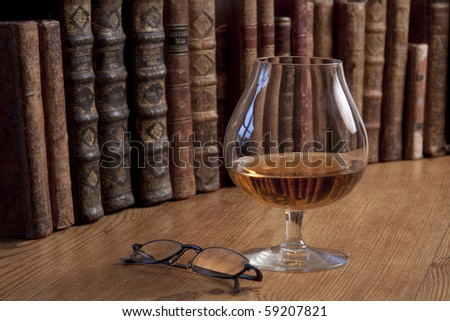 Vintage books standing in a row with a glass of cognac standing in front. - stock photo