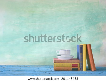 vintage books with coffee cup, grungy background, free copy space  - stock photo