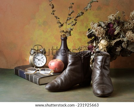 Vintage boots with alarm clock book apple and dry roses still life art - stock photo