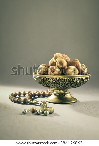 Vintage bowl of dates. Dates in a bowl and islamic prayer beads. - stock photo