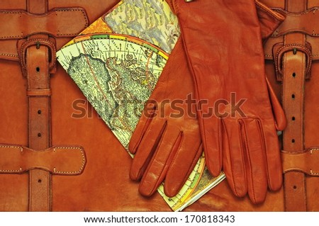 Vintage briefcase with leather gloves and old map  - stock photo