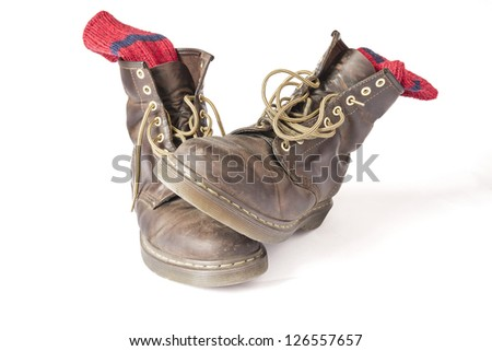 Vintage brown boots with red socks on a white background - stock photo