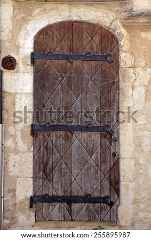 Vintage brown wood medieval door in rural stone wall house, Provence, France - stock photo