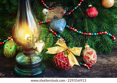 vintage burning lantern with decorated christmas evergreen wreath, low key - stock photo