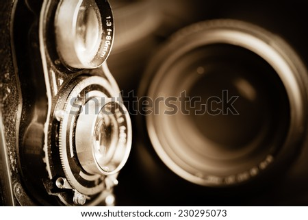 Vintage camera and lenses toned in sepia - stock photo