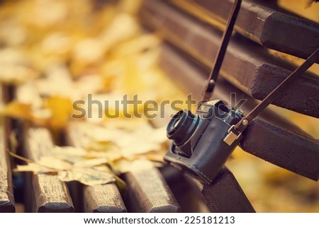 Vintage camera hanging on wooden bench in autumn park. Instagram style toned photo. - stock photo