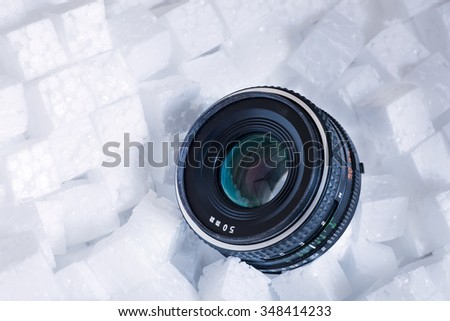 vintage camera lens is on the soft protection pieces of foam - stock photo