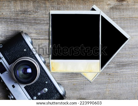 Vintage camera with blank old photograph on wooden background - Photography concept - stock photo