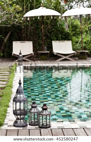 Vintage candle lamps standing near swimming pool. Summer in winter. Asian hotel - stock photo
