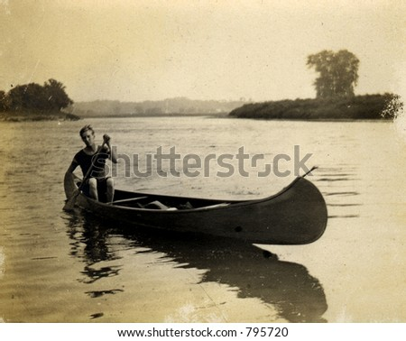 Vintage Canoe paddler. Circa 1909 print has many scratches, artifacts, fading, and solarization qualities. - stock photo