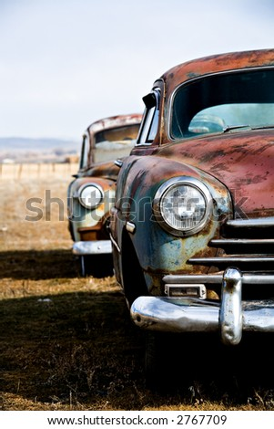 vintage car - two vintage cars abandoned on a field in rural wyoming. vertical version. - stock photo