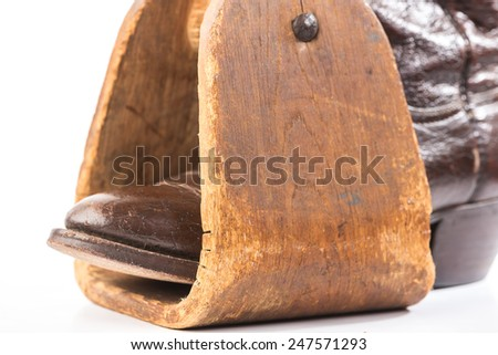 Vintage Caribou Hide Cowboy Boot in antique homemade wooden saddle stirrup against white background. Horizontal with copy space. - stock photo