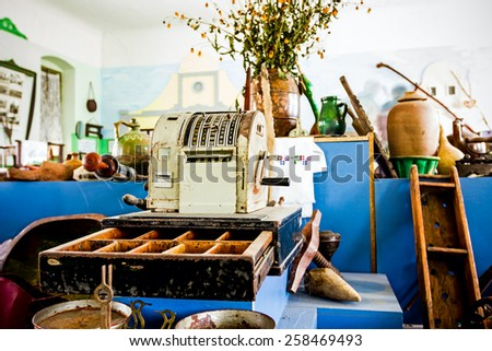 Vintage cash register with money drawer open surrounded with bunch of antiques. - stock photo