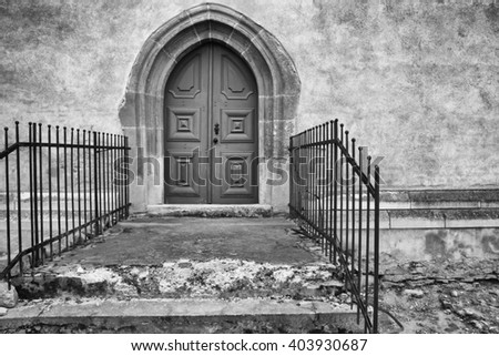 Vintage castle door and concrete wall in black and white - stock photo