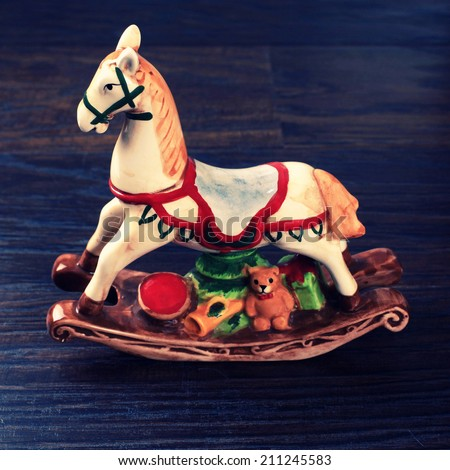 Vintage ceramic toy horse (christmas decoration also) on wood background, instagram effect - stock photo