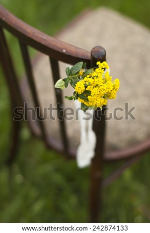 Vintage chair with a floral arrangement for wedding ceremony - stock photo