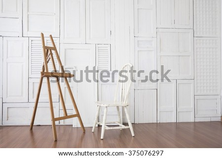 Vintage chair with paint stand in the room with white wooden window wall - stock photo