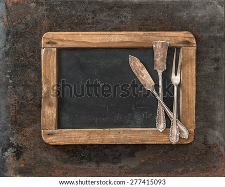 Vintage chalkboard and silver cutlery on rusted textured metal background. Antique tableware - stock photo