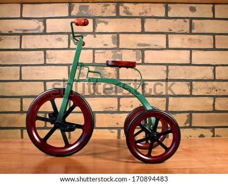 vintage child's tricycle against a brick background - stock photo