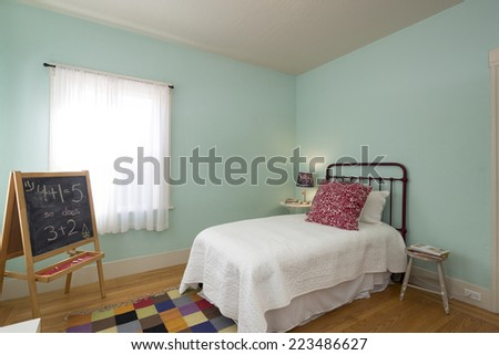 Vintage children bedroom / kids room with light turquoise light blue walls, carpet, chalkboard and window. - stock photo