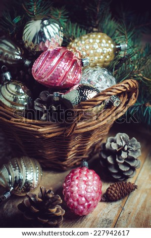 Vintage Christmas decorations in a wicker basket, Christmas gift in retro style, rustic home decor. - stock photo