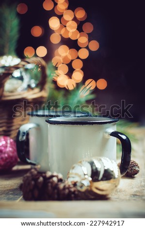 Vintage Christmas decorations in a wicker basket, two mugs of hot drink, Christmas garlands, cozy home decor. - stock photo