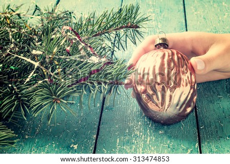 Vintage Christmas decorations in the form of gilded walnut in a female hand on a blue wooden background. Selective focus. Tinted photos - stock photo