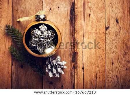 Vintage Christmas  decorations on wooden background. Golden ball and pine cone on old wood board with copyspace for greeting text. - stock photo