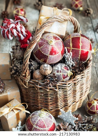 Vintage Christmas Gifts in Magic Composition with Basket. Red balls, Pine cones, Sweet Candy, Pine cones, Boxes, Walnuts and snowflakes. Country style - stock photo