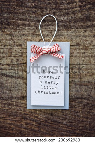 Vintage Christmas tag with ribbon and typewriter HAVE A MERRY LITTLE CHRISTMAS - stock photo