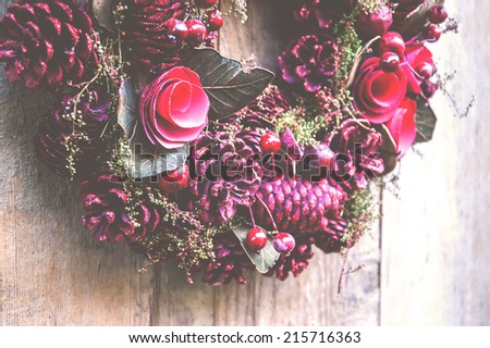 Vintage Christmas wreath with pine cones, flowers and red berries hanging on the grungy wooden door.  Greeting card. Aged photo. - stock photo