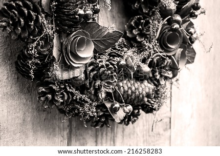 Vintage Christmas wreath with pine cones, flowers and red berries hanging on the grungy wooden door.  Greeting card. Aged photo. Black and white. - stock photo