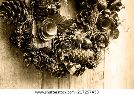 Vintage Christmas wreath with pine cones, flowers and red berries hanging on the grungy wooden door.  Greeting card. Aged photo. Sepia. - stock photo
