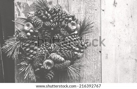 Vintage Christmas wreath with pine cones, sugared apples and red berries hanging on the grungy wooden door. Greeting card. Retro aged photo. Haze. Black and white. - stock photo