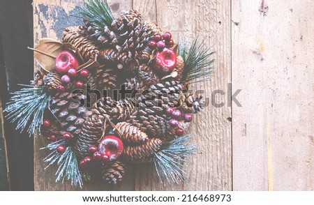 Vintage Christmas wreath with pine cones, sugared apples and red berries hanging on the grungy wooden door. Greeting card. Haze. - stock photo