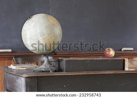 Vintage classroom showing blackboard behind apple and antique globe on teacher's desk  - stock photo