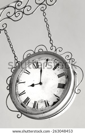 Vintage clock hanging from chains - stock photo